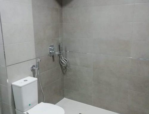 Baño con griferia empotrada y detalles en aluminio.
